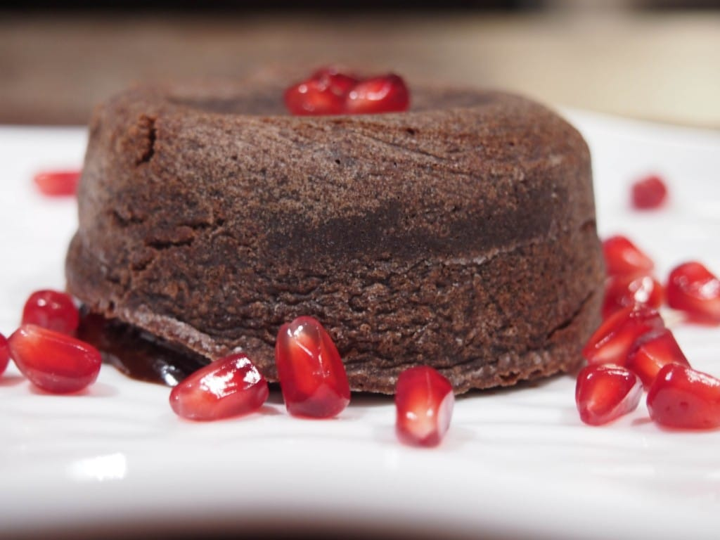 Molten Chocolate Cake on plate topped with pomegranate seeds.
