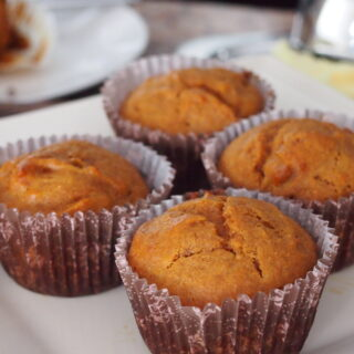 Four Carrot Muffins on white dish.