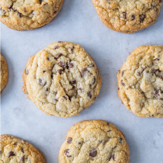Freshly baked chewy chocolate chip cookies on baking sheet.