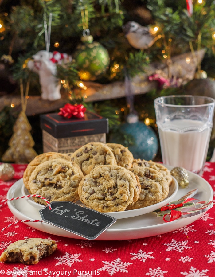Chewy chocolate chip cookies on dish with glass of milk for Santa.