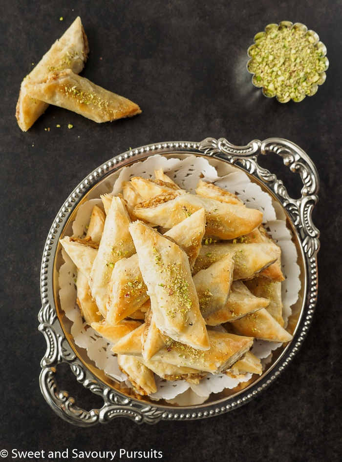 Rolled Baklava fingers piled on serving dish.