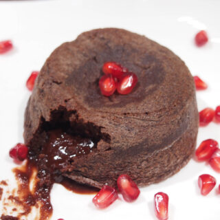 One Molten Chocolate Cake with view of oozing chocolate coming out of it.