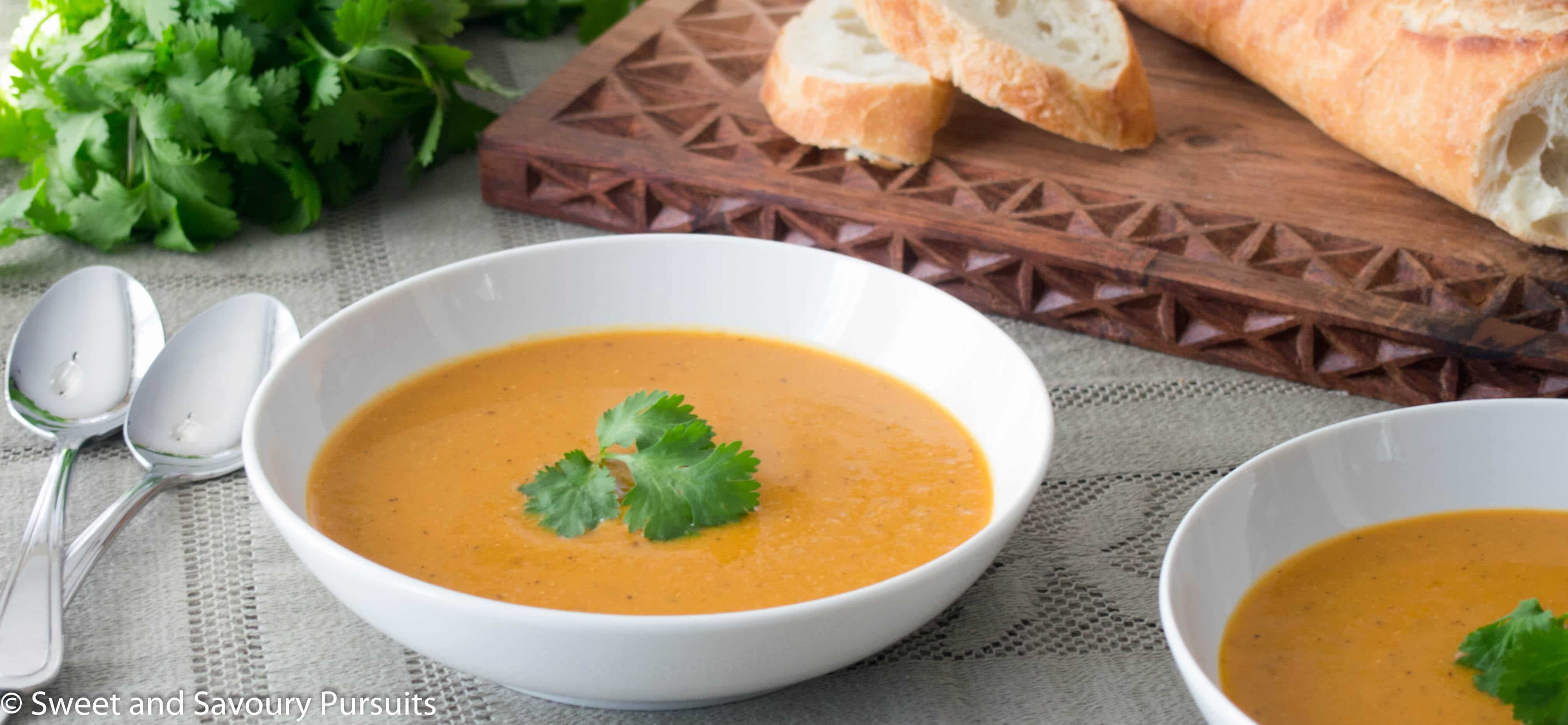 Puréed Red Lentil and Cauliflower Soup in two white bowls with bread on the side.