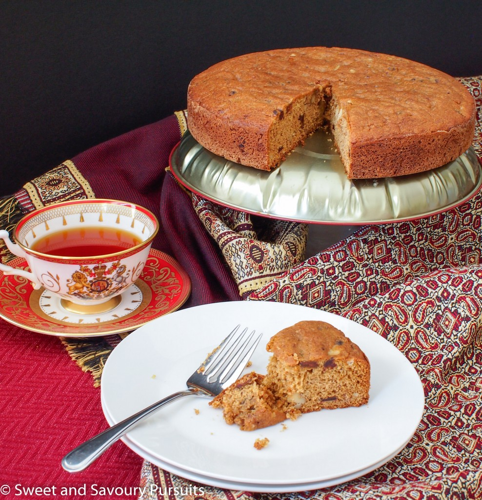 Partially eaten slice of date cake served with a cup of tea.