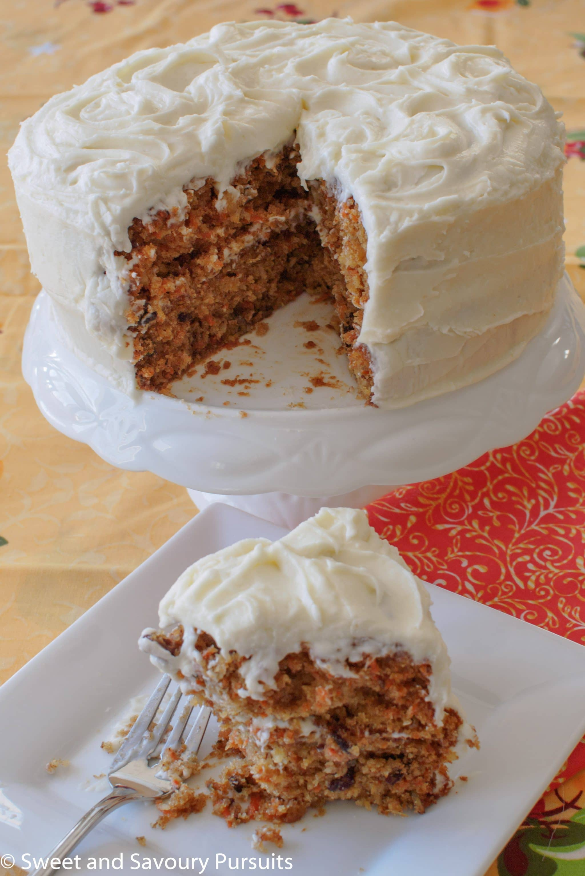 Carrot Cake with Cream Cheese Frosting on platter with slice removed.