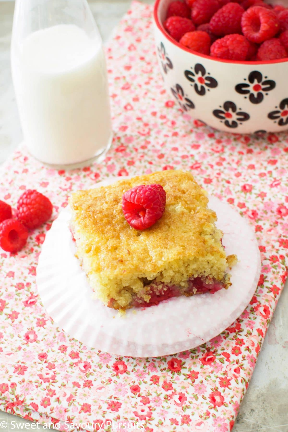Raspberry Buttermilk Cake served with bowl of fresh raspberries.