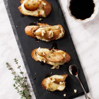 Pear and Brie Crostini drizzled with a honey and balsamic syrup and topped with crumbled walnuts and a sprinkle of fresh thyme leaves.