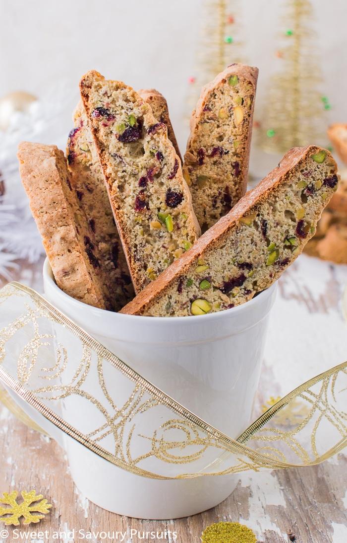 Pistachio and Cranberry Biscotti displayed in mug.