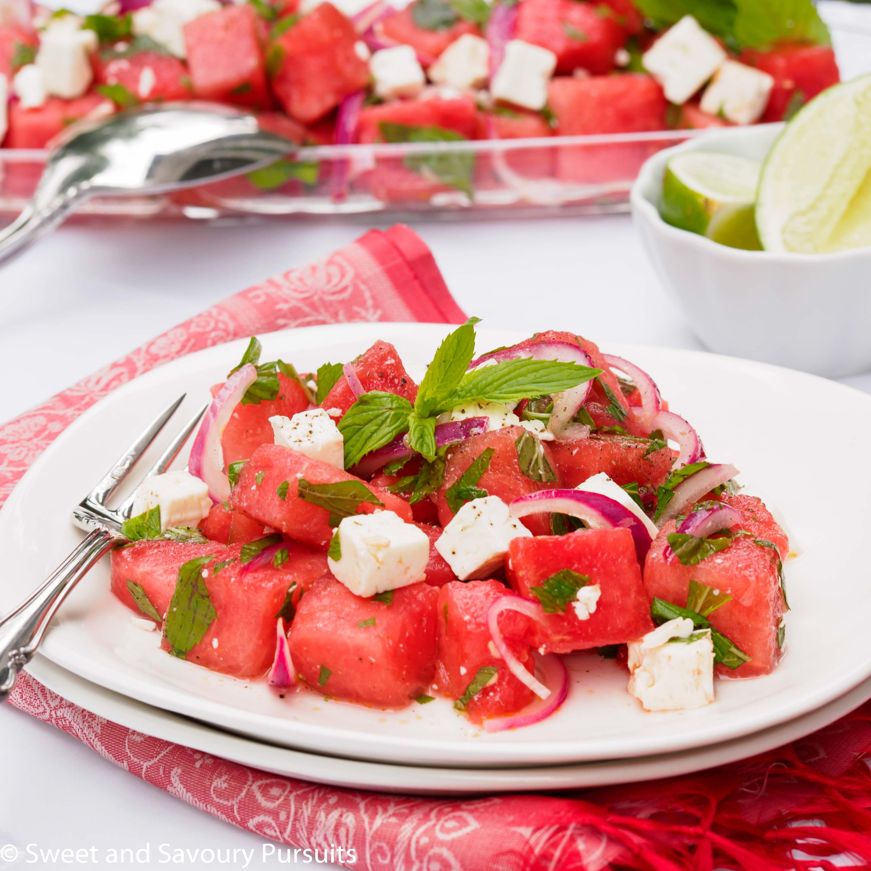 Salad made with cubed watermelon and feta cheese topped with fresh mint leaves and served on white dish.