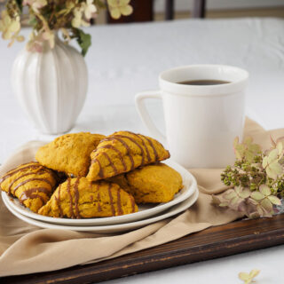 Plate of Pumpkin Scones on tray served with a cup of coffee.