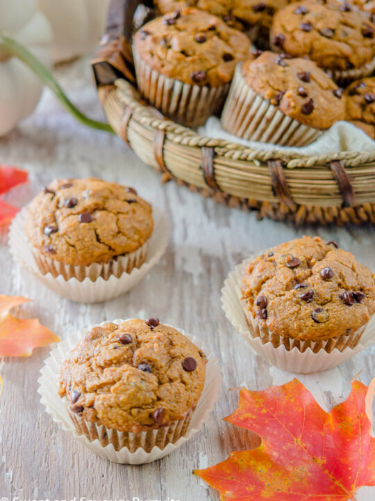 Three Pumpkin Chocolate Chip Muffins on a board with a basket of muffins in the background.