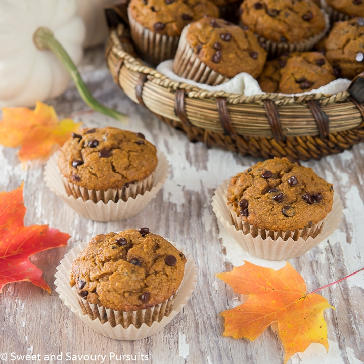 Whole Wheat Pumpkin Chocolate Chip Muffins on board with basket of muffins in the background.