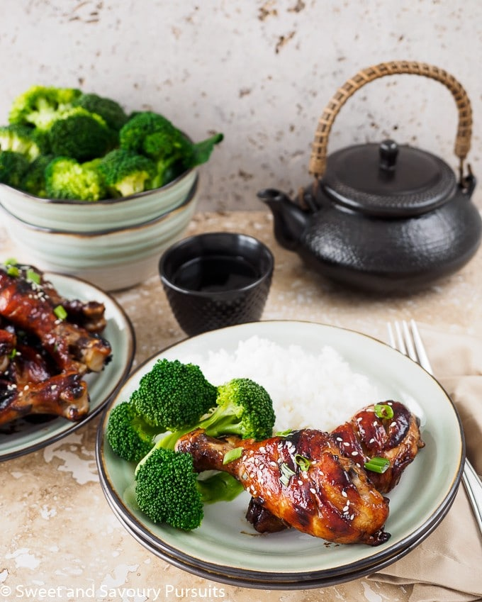 Sticky Chicken Drumsticks on dish with rice and broccoli.