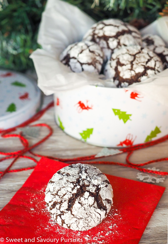 Tin of Chocolate Crinkle Cookies with cookie on napkin.