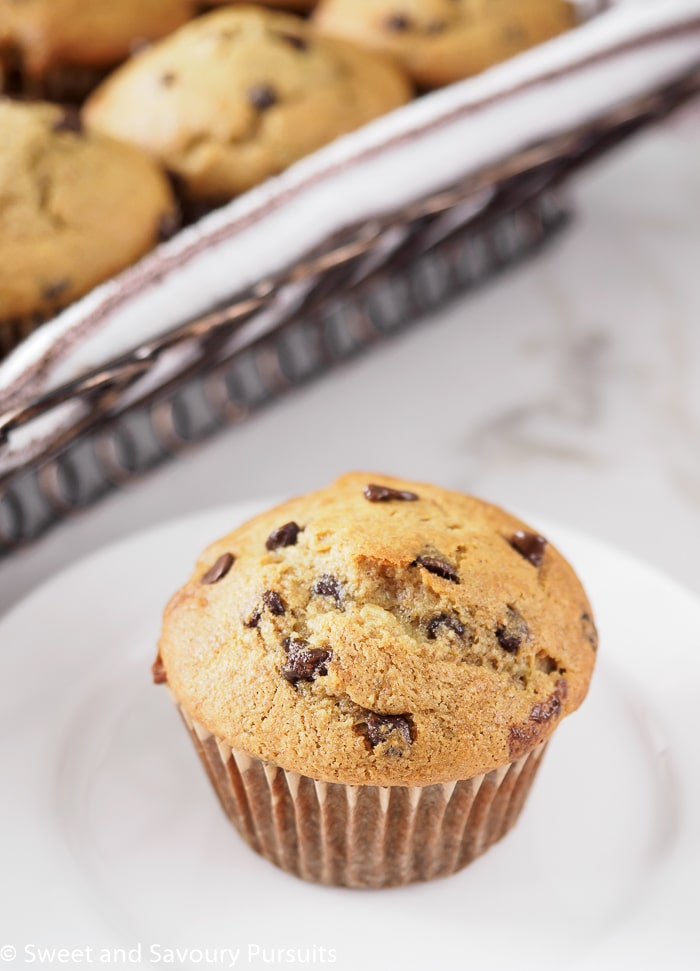 Banana Chocolate Chip Muffin on dish with basket of muffins in background.