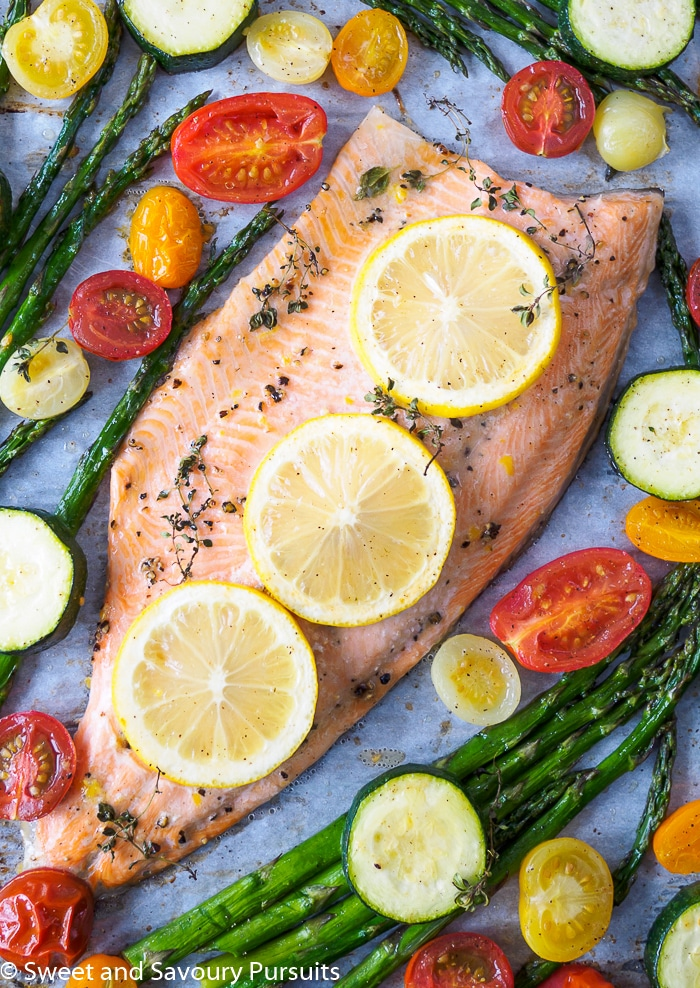 Baked Rainbow Trout Fillet with asparagus, cherry tomatoes and zucchini baked all on one tray.