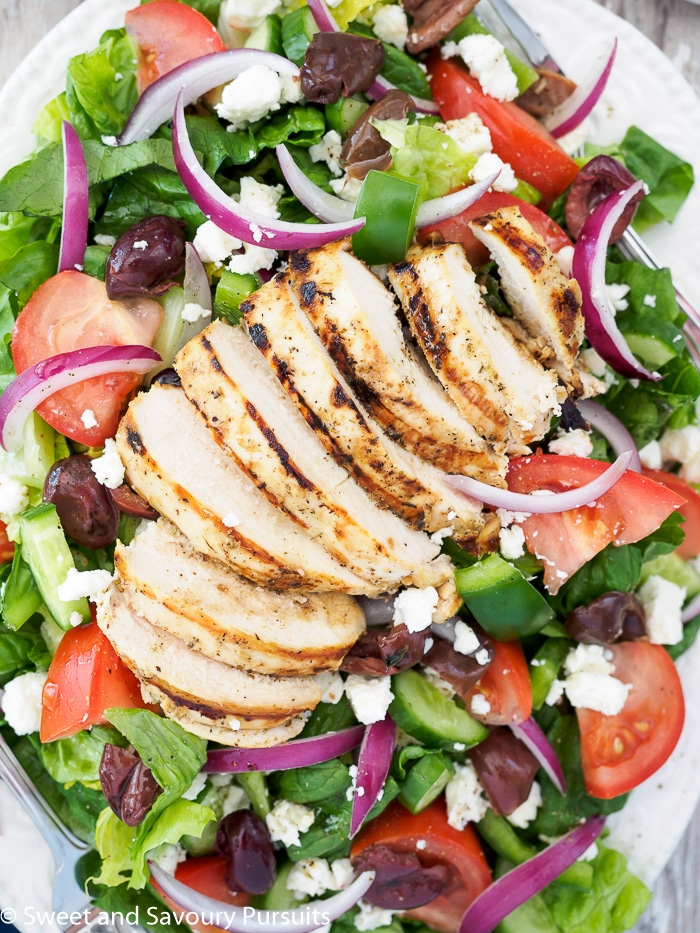 Platter with a grilled chicken breast on top of a green salad.