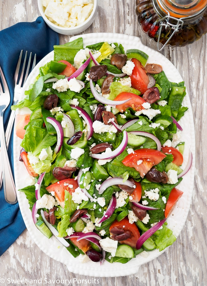 Greek style salad served on large white oval plate.