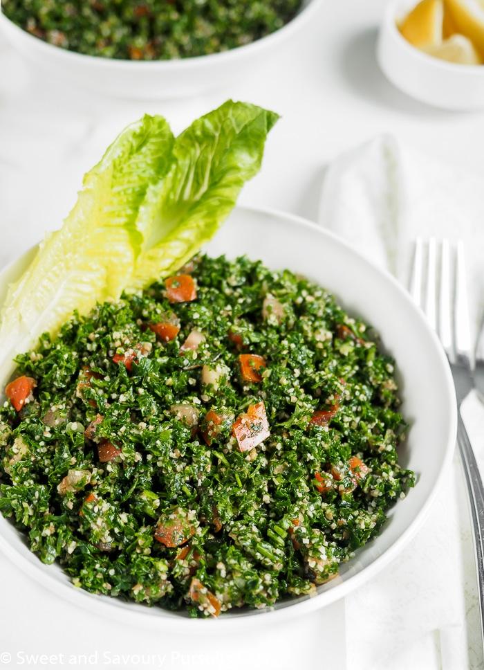 Lebanese Tabbouleh served in bowl with romain lettuce leaves.