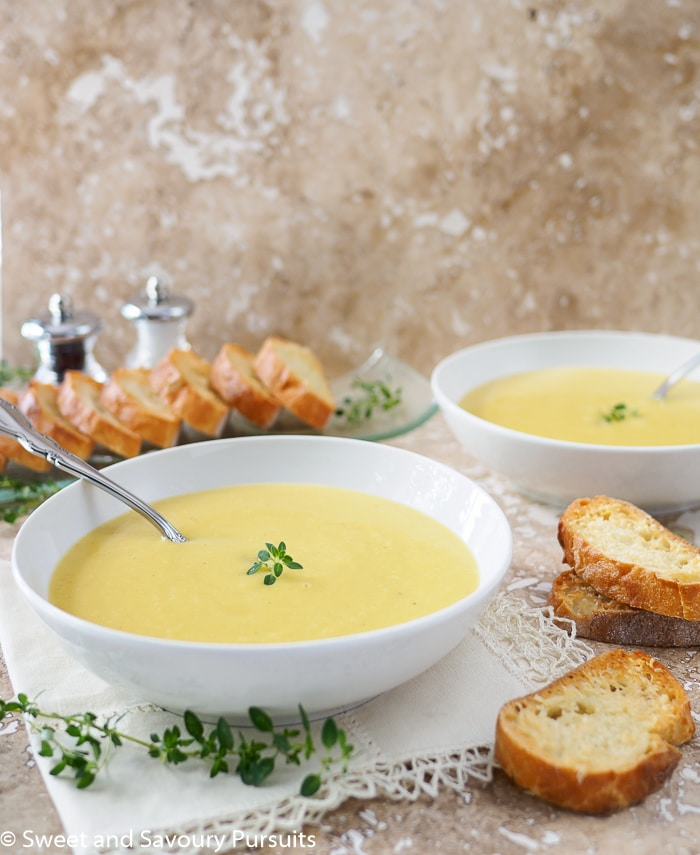 Bowls of Creamy Leek and Potato Soup served with Garlic Parmesan Crostini on the side.