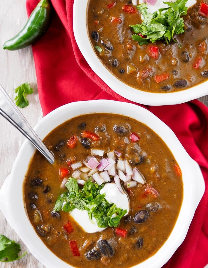 Bowls of Black Bean Soup topped with chopped cilantro, onion and sour cream.