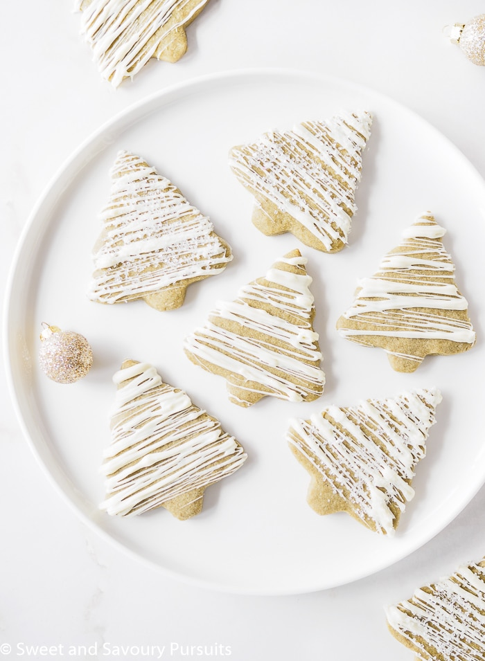 Matcha Sugar Cookies drizzled with white chocolate icing on white dish.