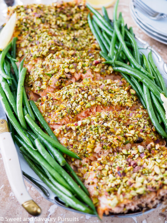 Fillet of Pistachio Crusted Salmon and green beans on serving dish.