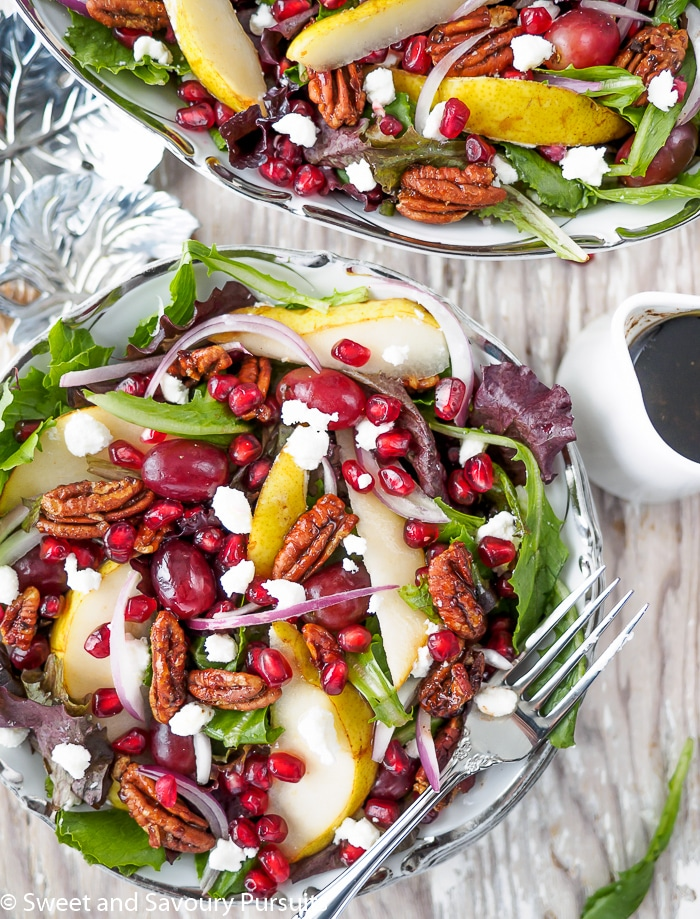 Top view of a salad with pomegranate seeds, pears, grapes and pecan.
