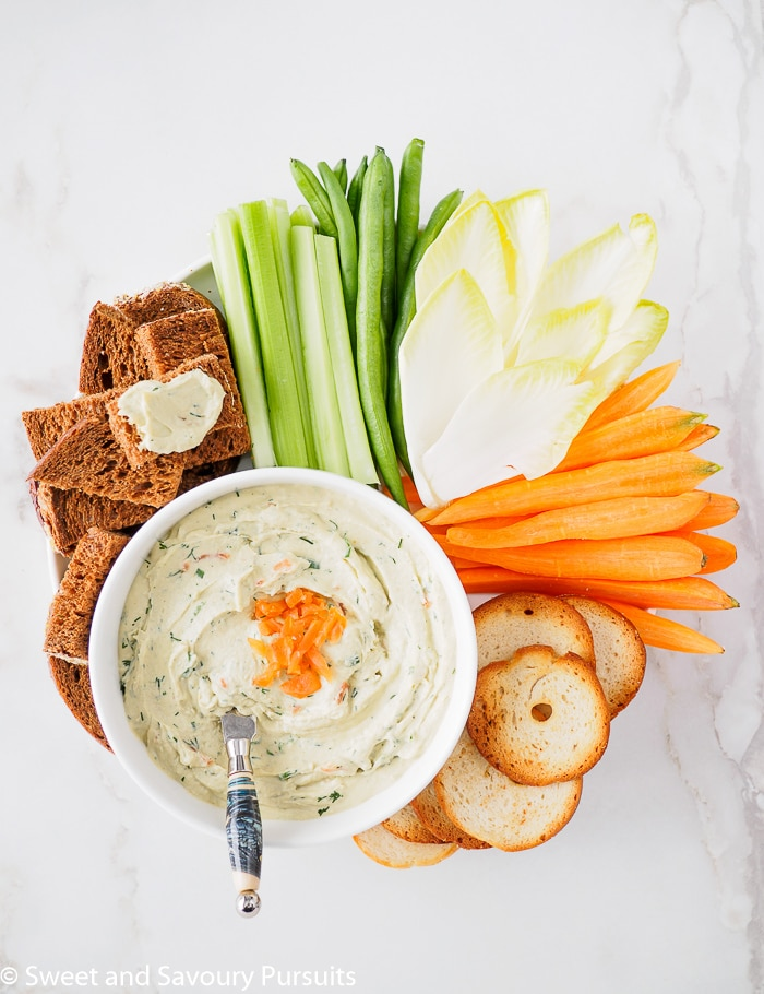 Top view of a bowl of Smoked Salmon and Cream Cheese Dip served with vegetables, pumpernickel bread and crackers.
