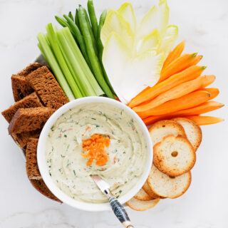 Smoked Salmon Cream Cheese Dip served with vegetables, pumpernickel bread, and bagel crisps