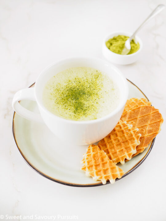 A large cup of Matcha Green Tea Latte served with cookies.