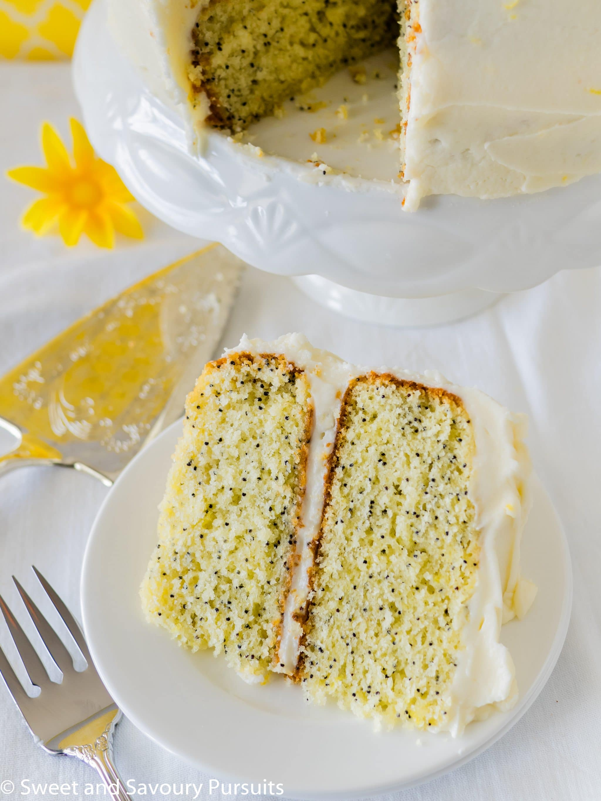 Slice of a layered Lemon Poppy Seed Cake with Cream Cheese Frosting.