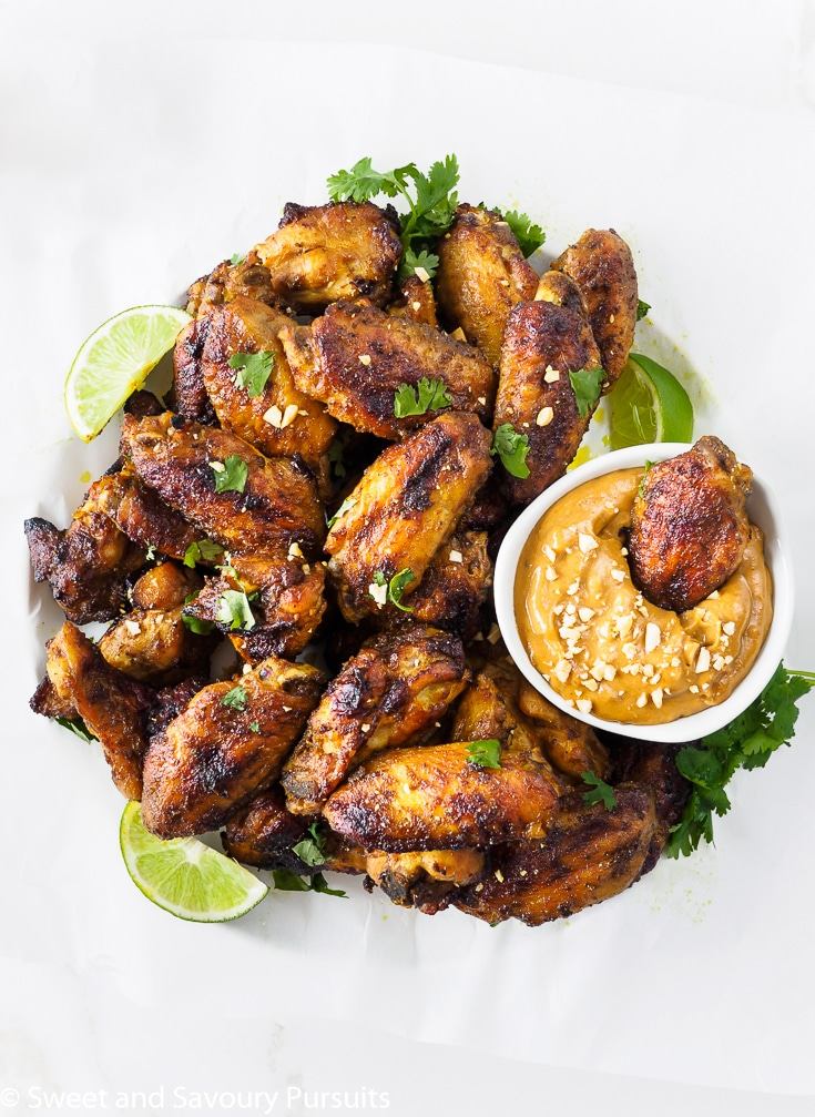 Platter of Thai Chicken Wings with a chicken wing dipped in a bowl of peanut sauce.