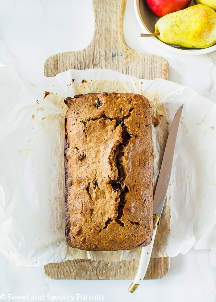 Pear, Date and Walnut Loaf on wooden cutting board.