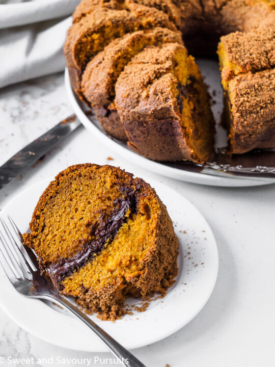 A plated slice of pumpkin cake with a chocolate swirl.