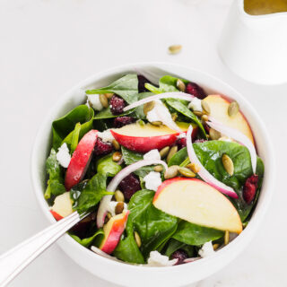 Small bowl of spinach salad with apple, dried cranberries and pumpkin seeds.
