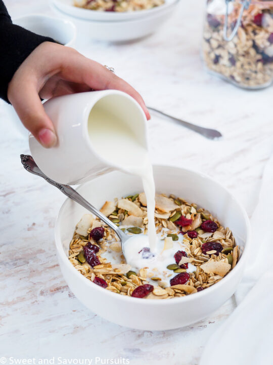 Bowl of homemade muesli being topped with milk.