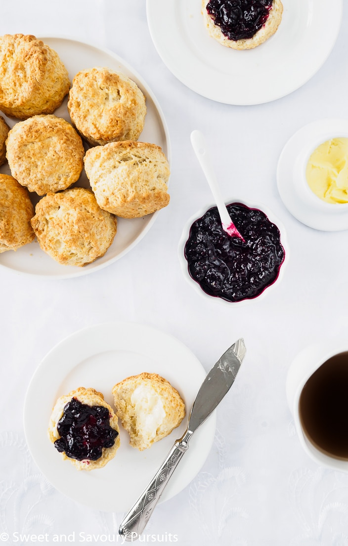 Dish of homemade Irish Scones served with butter and berry jam.