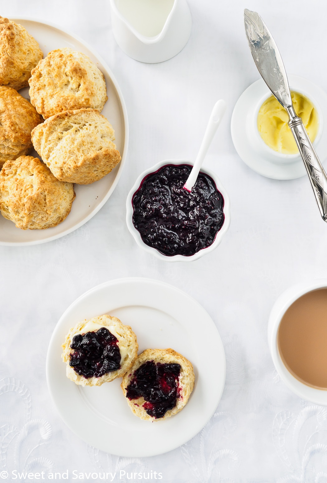 A dish of Irish Scones served with tea, butter and mixed berry jam.
