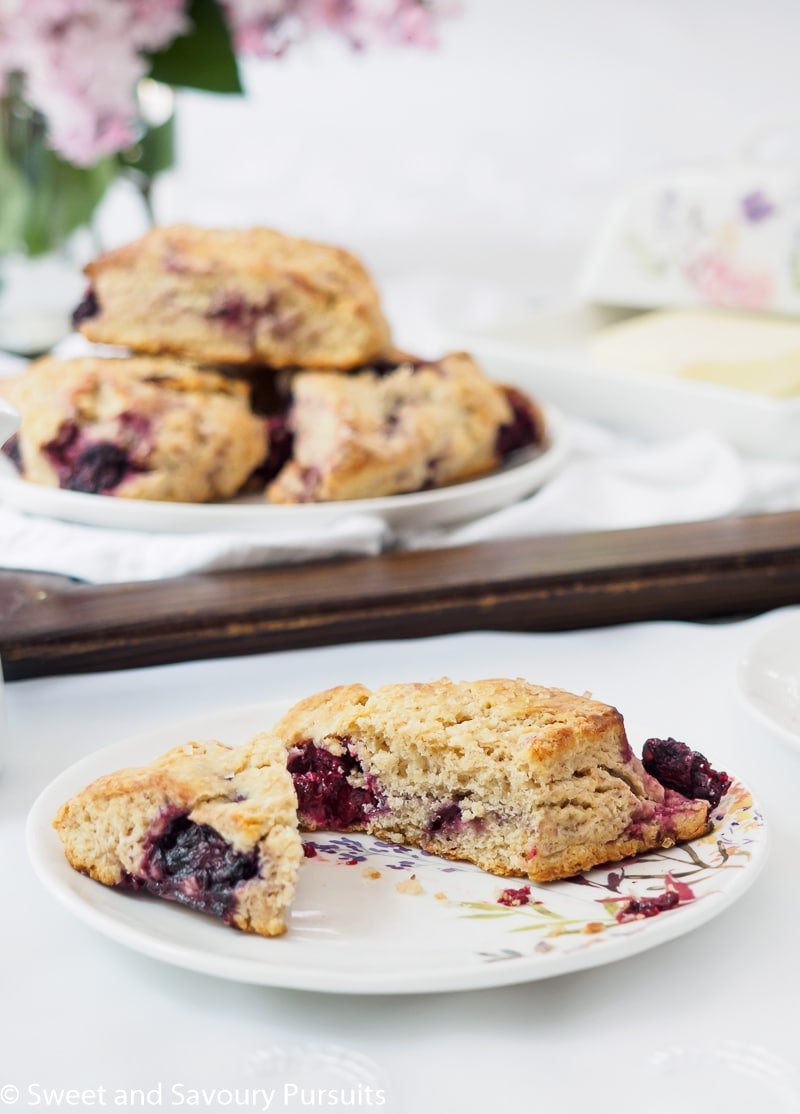Close-up of a plate with a cut Blackberry scone.