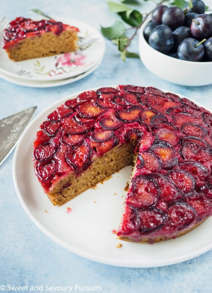 Plum Upside-Down Cake on white dish with slice removed to the side.
