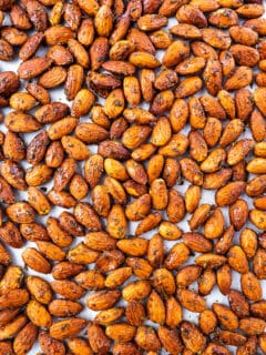 Roasted seasoned almonds on baking tray.