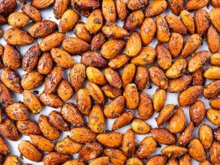 Roasted seasoned almonds on baking tray.
