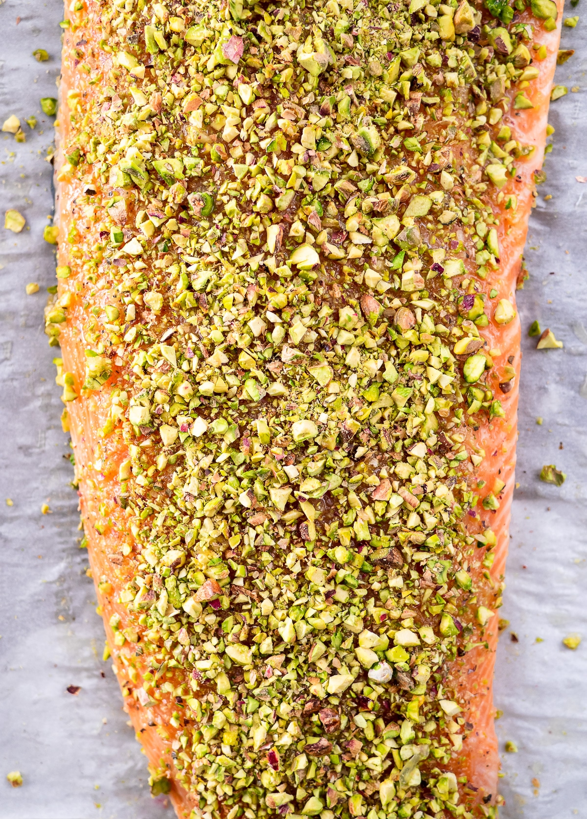 Raw filet of salmon crusted with chopped pistachios.